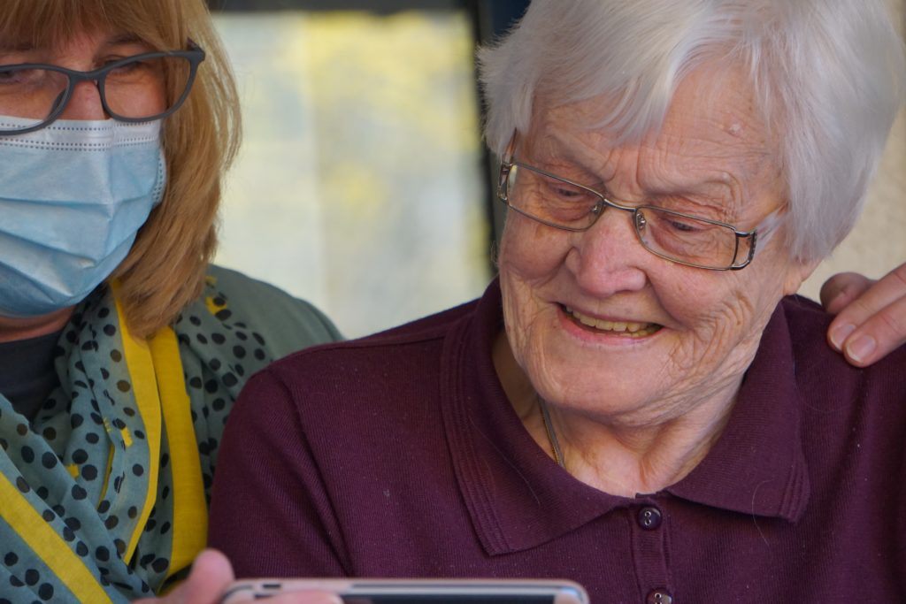 Woman with mask helping elder woman with videocall