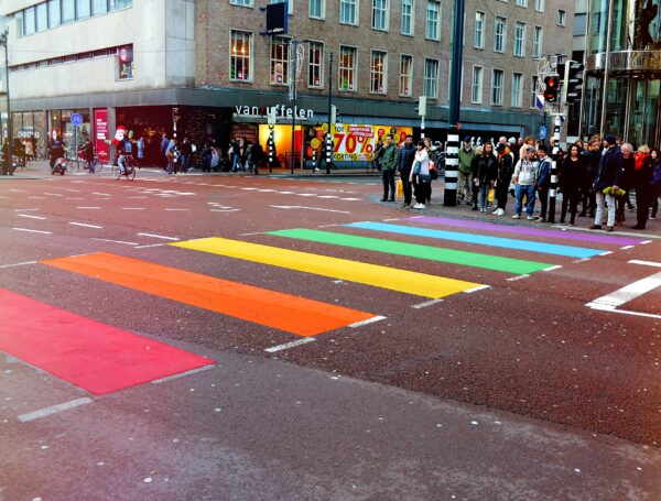An urban commercial road where many people are waiting to walk on coloured crossing lines