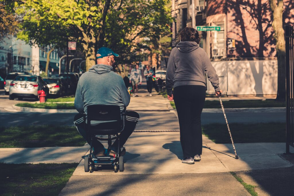 a blind woman with the aid-stick and a man on a wheelchair crossing an urban street in a sunny spring day